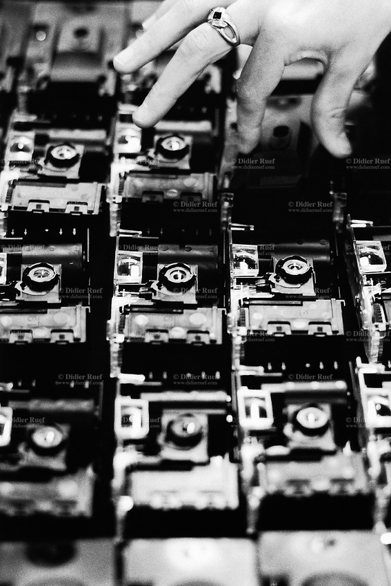 "France. Saône-et-Loire department. Chalon-sur-Saône. Kodak factory. Camera recycling. An handicapped woman works to dismantle, control and reassemble the cameras. The ""ready to take pictures"" camera is a small camera commonly described as disposable but in fact assembled for customers to return it after use. After being dismantled, verified and meticulously cleaned, some pieces are reused, other recycled (86%). The recycled parts are the front, film, upper and rear part, lens. The plastics parts are torn, melted, recasted and then reassembled.  Eastman Kodak Company. Chalon-sur-Saône is located in the south of the Burgundy region. © 1996 Didier Ruef .."