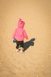 Toddler girl child alone on beach chasing shadow.