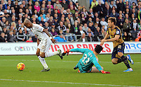 Andre Ayew of Swansea (L) gets past Petr Cech of Arsenal (C)  only for his shot to be saved by an Arsenal defender during the Barclays Premier League match between Swansea City and Arsenal at the Liberty Stadium, Swansea on October 31st 2015