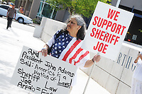 Phoenix, Arizona. July 24, 2012 - Martha Payan, a Sheriff Arpaio's supporter, demonstrates outside the Sandra Day O'Connor United States Federal Courthouse in Phoenix, Arizona with a sign in favor of enforcing United States laws as Sheriff Arpaio testifies in court. Maricopa County Sheriff Joe Arpaio testified in court on July 24, 2012 to respond to accusations his office (MCSO) has been racial profiling Latinos as they enforce local immigration laws in the county. The lawsuit is known as Ortega-Melendres vs. Arpaio. Photo by Eduardo Barraza © 2012