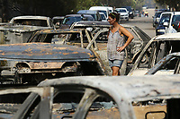 Pictured: A local woman stands in the middle of rows of destroyed cars in the aftermath of the wild forest fires in the Mati area near Rafina, Greece. Tuesday 24 July 2018<br /> Re: Deaths caused by wild forest fires throughout Greece.