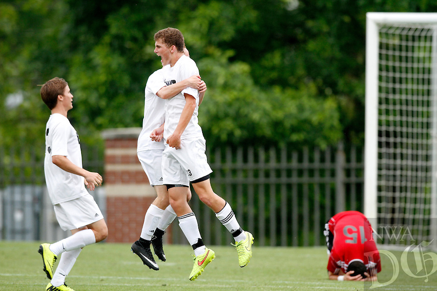 PHOTO BY SAMANTHA BAKER<br /><br />Connor Hanus, center, of Bentonville celebrates with teammates as Kareem Ihmeidan, right, of Fort Smith Northside collapses in defeat Saturday, May 23, 2014, after the 7A State Soccer championship at <br />Razorback Field in Fayetteville.
