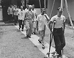 "HQ, Feaf, Tokyo -- Eleven happy U.S. Air Force men, who were shot down in their B-29 ""Superfort"" during a leaflet dropping mission over North Korea in January 1953, walk through the courtyard of the Jockey Club in Hongkong, where warm showers, a steak dinner and new clothes awaited them. They are shown here in their ""prison"" clothes. A short time later they were decked out in new U.S. Air Force uniforms that fit. A suitcase labeled with each man's name, was waiting on his bunk, containing both military and casual clothing, toilet, articles, pajamas, underwear and other necessities. 6 August 1955."