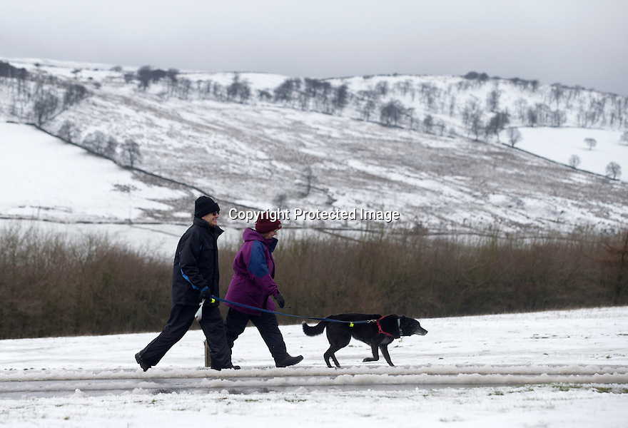 """28/03/16 <br /> <br /> Walkers near Grinlow Tower, Buxton.<br /> <br /> Holiday makers camping in the Derbyshire Peak District woke up to an unexpected white blanket this morning, thanks to Storm Katie.<br /> The covering of snow meant that many campers cut short their plans for a long weekend away, to brave the icy roads and head home early on Monday morning.<br /> But it wasn't all bad news for some of the younger guests at Grin Low Caravan Site in Buxton.<br /> Three-year-old Greta Williams made the most of the morning's surprise by building a snowman and enjoying snowball fights with her aunt Claire Jones. <br /> Claire said it was the first time she had been camping in the snow. <br /> """"It was completely unexpected but it's made it a trip to remember,""""she said. <br /> """"Greta really enjoyed making the snowman, but I think we'll head back home now in case any more falls.""""<br /> For Chris and Lorraine McCoy the first they knew of the snow was when they woke up and stuck their heads out of their tent.<br /> They had travelled to Buxton from Warwickshire with their four-year-old son Joe, to enjoy a weekend break.<br /> """"It's all part of the adventure,"""" said Chris. """"It's a bit cold in the tent but we'll soon warm up, and it's made the surrounding countryside really beautiful.""""<br /> <br /> All Rights Reserved: F Stop Press Ltd. +44(0)1335 418365   +44 (0)7765 242650 www.fstoppress.com"""