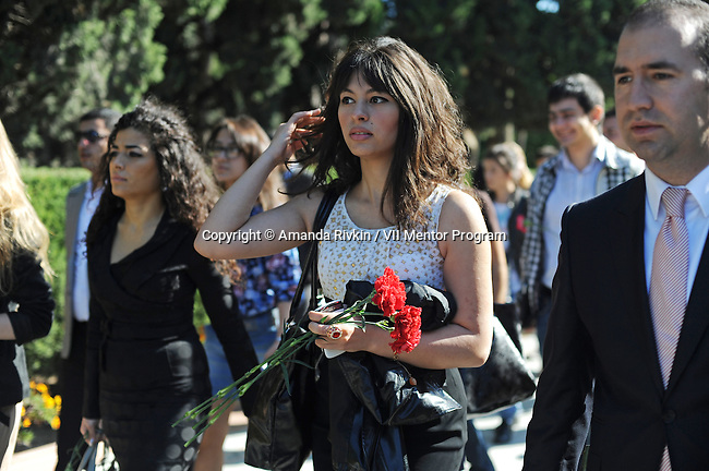 """Young women with the pro-government youth organization Ireli, translation, """"Forward,"""" bring red carnations to drop on the the tomb of Heydar Aliyev, the father of the current president of Azerbaijan, Ilham Aliyev, and the second president since the country's independence from the Soviet Union in 1991, during the second day of the World Youth Festival that brought young people from around the world to Azerbaijan as part of a week-long tour to showcase Azerbaijan and extol the virtues of the country and the culture to foreigners in Baku, Azerbaijan on October 14, 2011.  At right is Ceyhun Osmanli, a Member of Parliament and the Chairman of Ireli."""