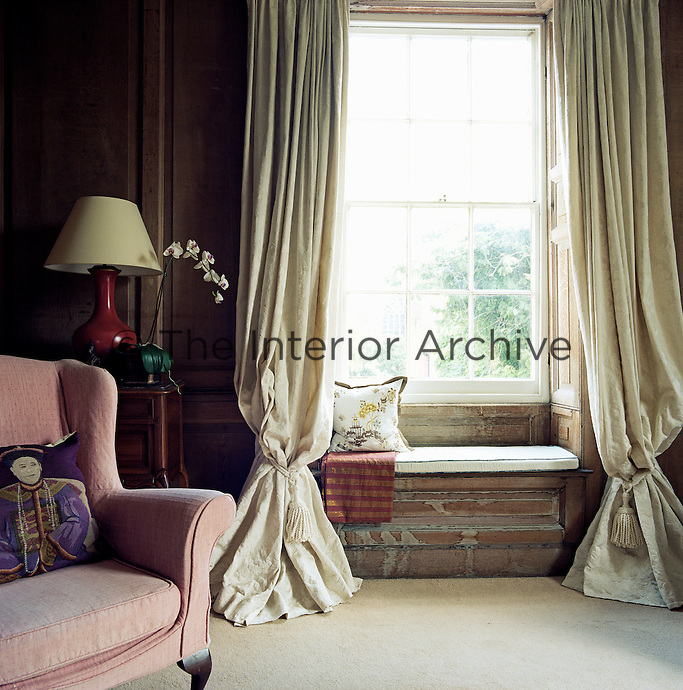 Voluminous cream curtains frame the large sash window in this oak panelled living room
