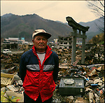 "Mr. Tadayoshi Tobai, 79, in front of a plot where there was his house in Otsuchi, Iwate, in one month after the earthquake and tsunami. ""Run away!"" he shouted to his wife who was in their house's garden when he saw the tsunami. She said she had to take something with her, and went inside the house. The tsunami was approaching toward their house at unbelievable speed. He ran up the hill toward to a shrine behind his house. ""The water collided with my house, making huge noise,"" he said"". ""I could not help her."" Floating propane gas started to explode and fire started all over the places. The fire went on for three days. ""It was a hell,"" he said. His wife's body is not yet found. He lives in the shrine behind his house and looks for wife's body everyday. His son who lives in the States flew back after tsunami, but could stay only one day and had to fly back to the States the next day. ""I would not leave here until I find my wife's body,"" he said. ""That is all I can do for her."" <br />