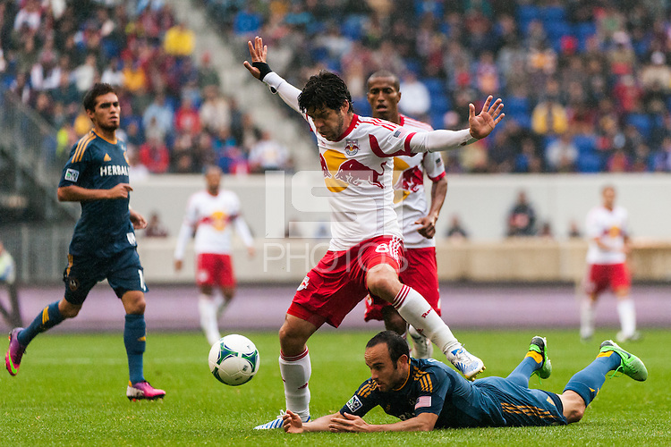 Juninho (8) of the New York Red Bulls looks to avoid a fallen Landon Donovan (10) of the Los Angeles Galaxy. The New York Red Bulls defeated the Los Angeles Galaxy 1-0 during a Major League Soccer (MLS) match at Red Bull Arena in Harrison, NJ, on May 19, 2013.