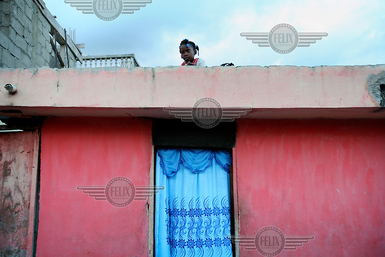 A child sits on the roof of a house in Cap Haitian.