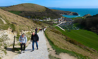 BNPS.co.uk (01202 558833)<br /> Pic: Graham Hunt/BNPS<br /> <br /> The car park a Lulworth Cove in Dorset was nearly full over weekend<br /> <br /> Fresh sea air and not a mask in sight - Visitors are not put off by the coronavirus pandemic and flock to Lulworth Cove on the Dorset Jurassic Coast on a sunny afternoon.<br /> <br /> Visitors walking along the South West Coast Path between Lulworth Cove and Durdle Door with a view towards Swyre Head and Bats Head.