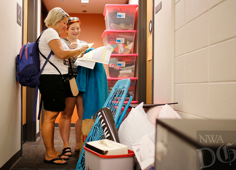 NWA Media/DAVID GOTTSCHALK - 8/20/14 - Antonia Greet, right, of Overland Park, KS., right, stands with her mother Mary and her belongings in the hallway of Hotz Honors Hall before entering her room Wednesday August 20, 2014 in front of Hotz Honors Hall on the campus in Fayetteville. Wednesday was Assisted Move-In Day for the Universtiy of Arkansas students. Move in started this past weekend with more than 5,000 students moving into residence halls this week.