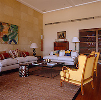 Two pale grey sofas situated on either side of a large metal coffee table are heaped with brightly coloured cushions