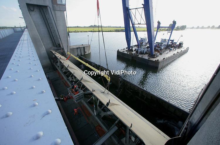 Foto: VidiPhoto..LITH - In opdracht van Rijkswaterstaat heeft aannemer Hollandia BV uit Krimpen a/d IJssel dinsdag de defecte stuwklep uit de sluis bij Lith getild. De klep, die begin 2007 beschadigd werd door een breuk in de hijskettingen, wordt vervangen door een authentieke constructie. De stuw Lith, gebouwd in de jaren dertig, bestaat uit drie schuiven die verticaal kunnen worden bewogen om het Maaswater te reguleren. De klep is 38 meter lang en heeft een gewicht van 55 ton.