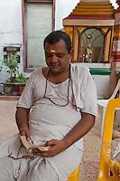 Stone Town, Zanzibar, Tanzania.  Hindu Priest, Kasyap Pandia, from Jamnagar, India, Reading Holy Text.  Ten years in Zanzibar.
