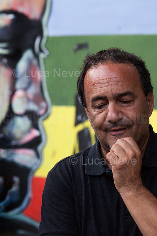 """Domenico 'Mimmo' Lucano (Mayor of Riace).<br /> <br /> Riace (Calabria, Italy), 04/08/2018. Visiting Riace for the third day of the """"Riace in Festival"""", 'Festival delle Migrazioni e delle Culture Locali' (Festival of Migration and Local Cultures). Attending the festival, amongst others, were the Mayor of Napoli Luigi De Magistris and the Mayor of Barcelona Ada Colau, debating with the Mayor of Riace, Domenico 'Mimmo' Lucano, about the so called """"migration crisis"""", as well as the now famous """"Modello Riace"""" (The Riace Model: how to welcome and work with Migrants to invest in building a future together). Other speakers included: Tiziana Barillà, Journalist at """"il Salto"""" (1) and Author of the book """"Mimi Capatosta. Mimmo Lucano e il modello Riace"""" (2),  Magistrates Riccardo De Vito and Emilio Sirianni (in turn President and Member of Magistratura Democratica). Chair of the event was Ilaria Bonaccorsi, Historian & Journalist at """"il Salto"""".<br /> From the Festival website: """"RIACE in FESTIVAL, is an event born in the wake of the policy of reception and resettlement of refugees and asylum seekers that the city administration of the """"Riace Bronzes'"""" town has been implementing for years. [...] The festival aims to be a concrete initiative that, through the universal language of cinema and the arts, promotes the exchange and mutual knowledge to counteract forms of closure and racism, drawing attention to the innovative path that the municipal administration of Riace has started by combining the reception of migrants with the revival of its territory and giving the image of an unpublished Calabria, different from that of the black chronicle>>.<br /> Riace is a small village in the province of Reggio Calabria. It's famous because on the 16 August 1972 Stefano Mariottini, a chemist from Rome, found two full-size Greek bronzes... (Riace Bronzes: https://bit.ly/2oBoFNY)<br /> (For the full caption read the ARTICLE at the the beginning of this story)"""