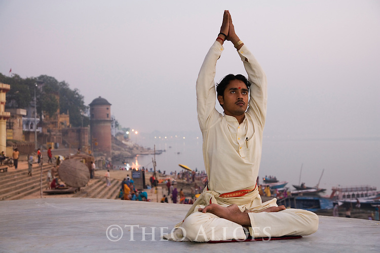 Yoga teacher doing his morning exercise at one of the Ghats (steps) in Varanasi;  Varanasi has been a cultural and religious center in northern India for several thousand years, Varanasi, Uttar Pradesh, India --- Model Released