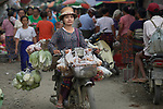 A woman rides a motorcycle through the Tahan Market in Kalay, a town in Myanmar. This market is located in Tahan, the largely ethnic Chin section of the town. The woman is wearing thanaka, a cosmetic paste, on her face.