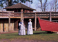 Fort Langley National Historic Site, BC, British Columbia, Canada - Female Re-enactors posing at Bastion and Supply Bateau.  Fort Langley was founded in 1827 as a Hudson's Bay Company Trading Post.