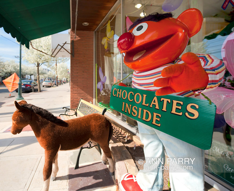"""MERRICK April 7, 2010: Ernie Doll holding """"Chocolates Inside"""" sign in closeup, and Pony Doll under awning, with benches, to attract customers to Merrick Flower Shoppe, Merrick, New York, USA"""