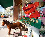"MERRICK April 7, 2010: Ernie Doll holding ""Chocolates Inside"" sign in closeup, and Pony Doll under awning, with benches, to attract customers to Merrick Flower Shoppe, Merrick, New York, USA"