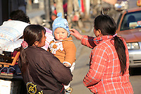 Two women and a baby chat in Shanghai, China, on January 10, 2009. Photo by Lucas Schifres/Pictobank