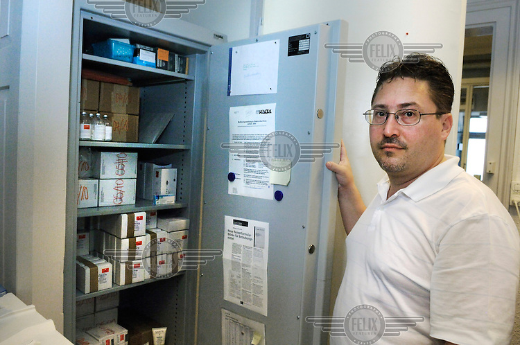 Doctor Adrian R. Korman head of ZOKL II, a clinic which distributes heroin to addicts under a supervised programme shows the safe in which heroin in powder and pill form, as well as methodone, is stored.