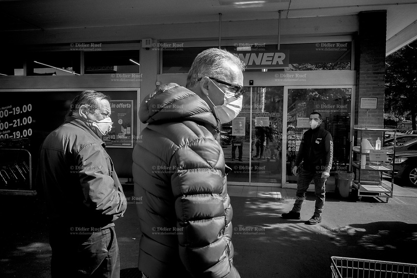 "Switzerland. Canton Ticino. Lugano. A worker stands at the entrance of Denner Supermarket. The man and various customers wear a mask on their faces to protect themselves from the Coronavirus (also called Covid-19). The worker's job is to control the door and and let enter only a restricted number of customers. Due to the spread of the coronavirus, the Federal Council has categorised the situation in the country as ""extraordinary"". It has issued a recommendation to all citizens to stay at home, especially the sick and the elderly. The Federal Council (German: Bundesrat, French: Conseil fédéral, Italian: Consiglio federale, Romansh: Cussegl federal) is the seven-member executive council that constitutes the federal government of the Swiss Confederation. From March 16 the government ramped up its response to the widening pandemic, ordering the closure of bars, restaurants, sports facilities and cultural spaces. Only businesses providing essential goods to the population – such as grocery stores, bakeries and pharmacies – are to remain open. Denner is a discount supermarket chain in Switzerland. It is Switzerland's third largest supermarket chain with 11.4% market share. It is owned by the Federation of Migros Cooperatives since 2007. 17.03.2020 © 2020 Didier Ruef"