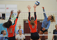 NWA Democrat-Gazette/ANDY SHUPE<br /> Klaire Trainor (22) of Springdale Har-Ber send the ball past C.J. Landram (9) and Shanice Erby (15) of Rogers Heritage Thursday, Sept. 17, 2015, at Wildcat Arena in Springdale. Visit nwadg.com/photos to see more photographs from the game.