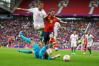 01.08.2012 Manchester, England. Spain midfielder Juan Mata, Morocco goalkeeper Mohamed Amsif and Morocco defender Zouhair Feddal in action during the third round group D mens match between Spain and Morocco at Old Trafford.