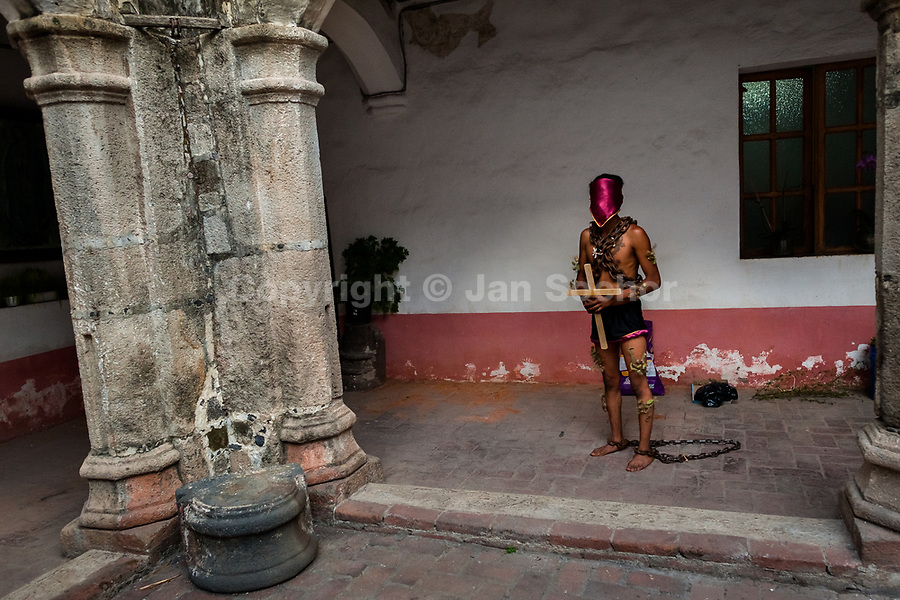 A chained Catholic penitent, holding a wooden cross, prepares to participate in the Holy week procession in Atlixco, Mexico, 30 March 2018. Every year on Good Friday, dozens of anonymous men of all ages voluntarily undergo pain and suffering during the religious procession of the 'Engrillados' (the Shackled ones) in Puebla state, central Mexico. Wearing heavy chains on their shoulders covered with prickling cacti while being burned by the hot midday sun, they recall Jesus Christ's death by crucifixion and demonstrate their religiosity and faith.