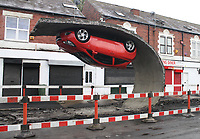 Alex Chinneck Hanging Car Artwork appears in Tinsley, Sheffield.<br /> <br /> The Artwork called 'Called Pick Yourself Up and Pull Yourself Together', the installation will be in place for just under a week.  <br /> <br /> The Artwork includes 15 meters of tarmac pulled back with a Vauxhall Corsa on the end. <br /> <br /> Pictures Alex Roebuck / www.alexroebuck.co.uk