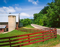 Vernon County, WI: County road passes a red fence and barn on an Amish farm in summer