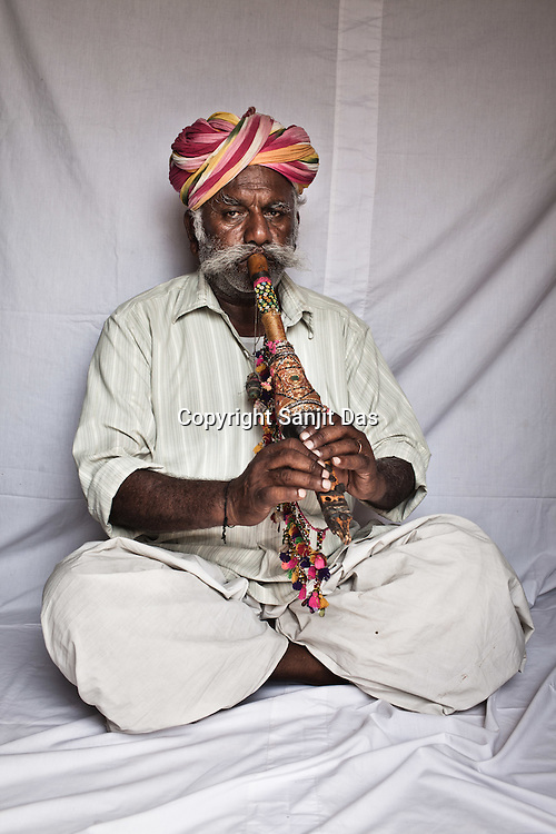 66-year-old Manganiyar artist and a Surnai player, Pempa Khan poses for a portrait inside his house in Hamira village of Jaiselmer district in Rajasthan, India. Photo: Sanjit Das/Panos