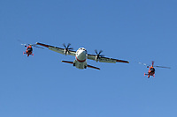 A pair of Coast Guard MH-65 Dolphin helicopters from Air Station San Francisco fly in close formation with a C-27J Spartan from Air Station Sacramento.