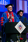 The Rev. Dennis H. Holtschneider, C.M., president of DePaul University confers the graduates degrees for Ray Whittington, dean of the Driehaus College of Business, Sunday, June 11, 2017, during the DePaul University Driehaus College of Business commencement ceremony at the Allstate Arena in Rosemont, IL. (DePaul University/Jamie Moncrief)
