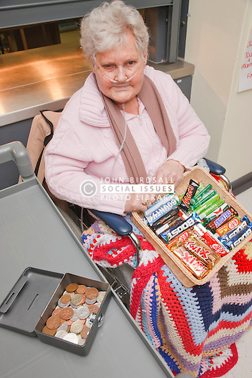 Service user in wheelchair, with complex disabilities, selling sweets in tuck shop at a resource for people with physical and sensory impairment.