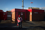 A solitary home supporter waiting outside a turnstile Wincham Park, home of Witton Albion before their Northern Premier League premier division fixture with Warrington Town. Formed in 1887, the home team have played at their current ground since 1989 having relocated from the Central Ground in Northwich. With both team chasing play-off spots, the visitors emerged with a 2-1 victory, the winner being scored by Tony Gray in second half injury time, watched by a crowd of 503.