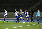 Watched by the additional assistant referee and a television cameraman, home striker Gojko Kacar (without shirt) is congratulated by teammates after scoring the only goal as Hertha Berlin take on Sporting Lisbon at the Olympic Stadium in Berlin in the group stages of the UEFA Europa League. Hertha won the match by 1 goal to nil to press to the knock-out round of the cup. 2009/10 was the the first year in which the Europa League replaced the UEFA Cup in European football competition.