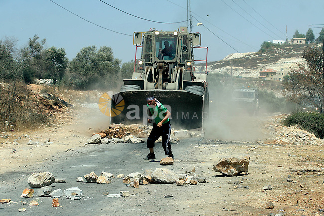 A Palestinian protestor throws stones at Israeli truck during a demonstration against the expropriation of Palestinian land by Israel in the village of Kafr Qaddum, near the West Bank city of Nablus on Aug. 03, 2012. Photo by Nedal Eshtayah