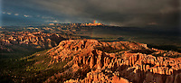 904000041 panormaic view of a rainbow over the hoodoos of bryce canyon national park during a summer monsoon rainstorm with ominous clouds in the background in utah united states