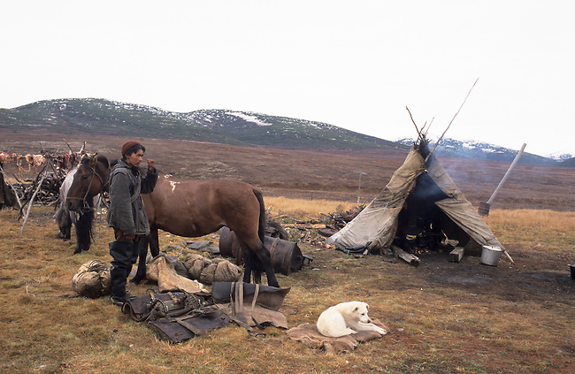 A young Chukchi man at a reindeer herder's autumn camp on the tundra near Khailino. Koryakia, Kamchatka, Siberia, Russia