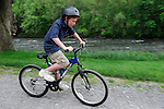 A red haired boy, wearing a helmet, rides his bike on the road along the creek.