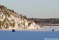 Ice fishing huts on a frozen lake on a sunny winter day