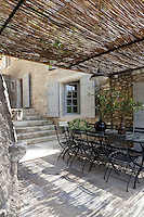 Stone steps lead from the house down to the terrace and an outdoor dining area
