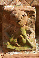 Norman Romanesque exterior corbel no 28 (similar style to No 44) - sculpture of a female exhibitionist known as a Sheela-na-gig. The sculpture shows a female with a huge round head and puny body with her hand holding open a grossly enlarged vulva. It seems unlikely that this image is of a pornographic nature because it is on a church, and is more likely a warning against the temptations of women. The Norman Romanesque Church of St Mary and St David, Kilpeck Herefordshire, England. Built around 1140