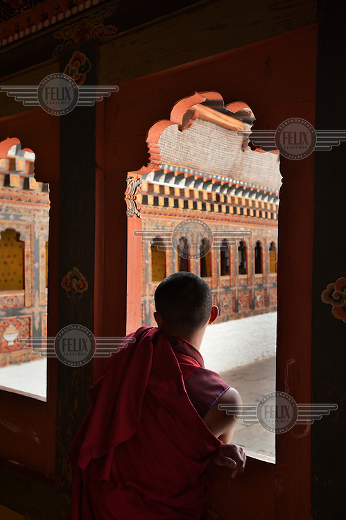 A monk looks out of an ornate window at the Tango Dzong Monastery.