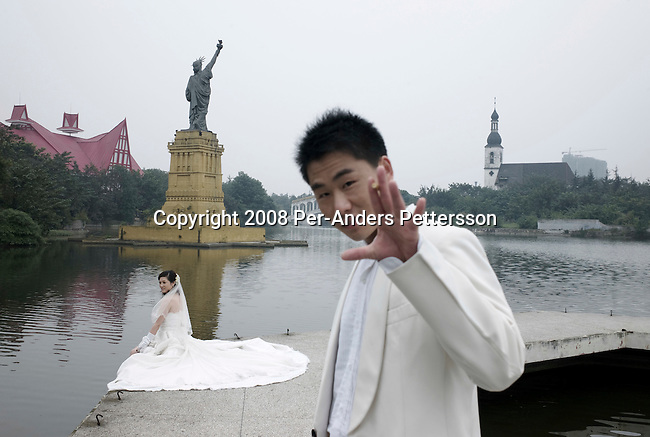 CHENGDU, CHINA OCTOBER 9: A bridegroom smokes a cigarette while his bride pose for a wedding photographer in front of a copy of The Statue Of Liberty at Chengdu World Paradise Theme Park on October 9, 2008 in Chengdu, China. The park closed in 2004 due to lack of funds and visitors. Some of the attractions are still there such as a Statue Of Liberty and Rialto bridge from Venice, Italy. Now its serves as a College and many students and teachers live there. It's also a popular place for taking wedding photos for local couples. Chinese people love theme parks and new ones are opening constantly. It's estimated that there's about 2400 theme parks in the country. Because of the tougher competition, some parks close down. (Photo by Per-Anders Pettersson) .
