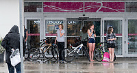 A torrential downpour is enough to keep cyclists off the streets, but lightening and thunderstorm is enough to request a ride home. <br /> Vanessa Sweeney and Jacinda Mcclintoc, wearing glasses, wait under a Lambton Mall awning while waiting for a ride home from shopping.