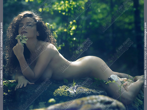 Sensual erotic portrait of a beautiful sexy nude woman with a wild flower in her hand lying naked on rocks in a deep forest inhaling the sweet aroma of the blooming plants
