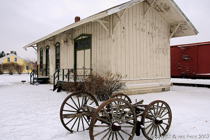 Classic 19th Century railroad station with spoked wheeled luggage cart carrier in winter scene.